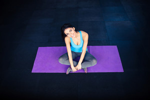 Happy fit woman sitting on yoga mat