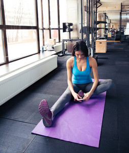 Young woman sitting on the yoga mat and using smartphone