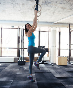Smiling woman working out on gimnastic rings