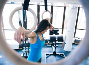Tired woman working out on gimnastick rings