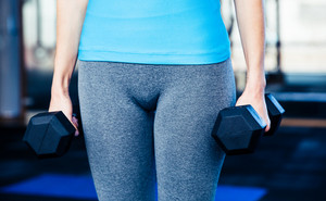 Closeup image of a woman standing with dumbbells