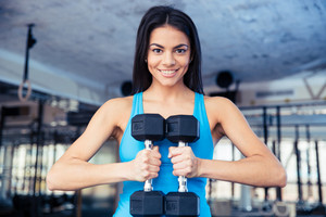 Happy fit woman holding dumbbells