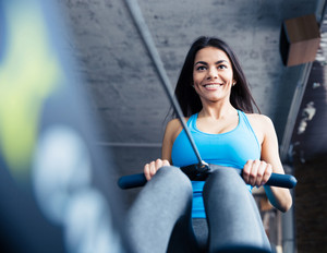 Happy charming woman working out at gym