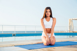 Girl sitting on yoga mat outdoors