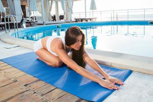 Girl doing yoga exercises on mat