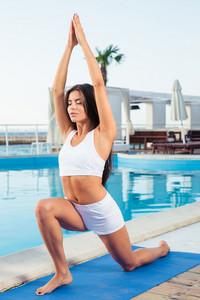 Woman doing yoga exercises on mat