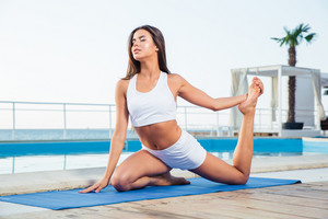 Woman doing yoga exercises outdoors