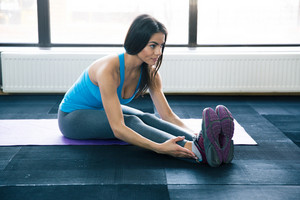 Young woman doing yoga exercises on yoga mat