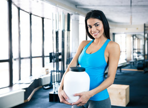 Happy woman holding plastic container with sports nutrition