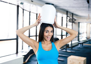 Laughing young fit woman with plastic container on head