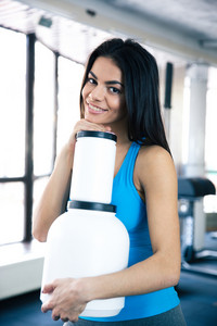 Smiling woman at gym with sports nutrition