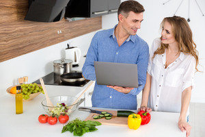 Happy couple using laptop and preparing vegetarian dishes