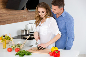 Beautiful couple making salad and flirting