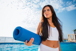 Beautiful woman holding yoga mat