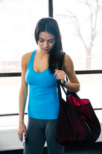 Young fit woman with bag in gym