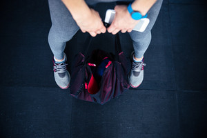 Woman holding fitness bag and smartphone