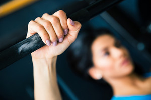Woman working out with barbell. focus on barbell