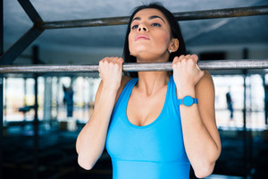 Charming woman working out on horizontal bar