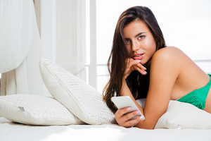 Girl in bikini lying on the bed with smartphone
