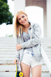 Happy girl standing on stairs with skateboard