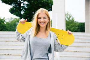 Smiling woman holding skateboard