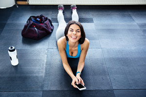 Fit woman lying on the floor and showing her tongue