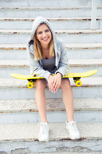 Girl sitting on the stairs with skateboard