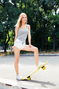 Cheerful young woman standing with skateboard