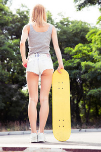 Back view portrait of a girl standing with skateboard outdoors