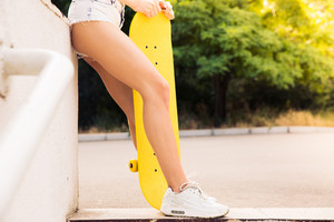 Female legs with skateboard
