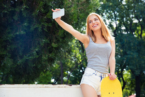 Happy girl with skateboard making selfie photo