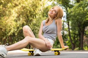 Young girl resting on skateboard