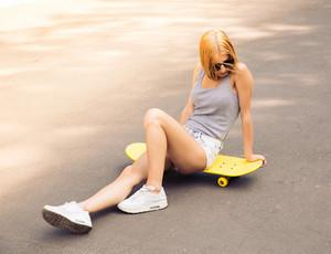 Girl in sunglasses sitting on skateboard outdoors