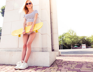 Happy female teenager holding skateboard