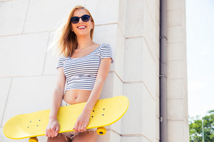 Female teenager standing with skateboard