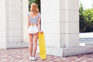 Girl in shorts holding skateboard outdoors