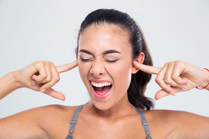 Woman covering her ears with fingers and shouting