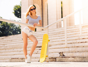 Female skater in sunglasses standing outdoors