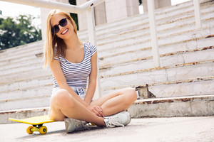 Female skater sitting on skate outdoors