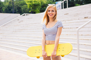 Cute girl standing with skateboard