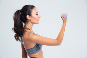 Happy fitness woman working out with dumbbells