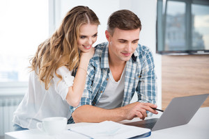 Beautiful couple using laptop and working together