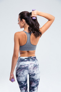 Back view portrait of a fitness woman working out with small dumbbells