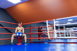 Boxer sitting in boxing ring