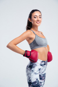 Smiling fitness girl standing in boxing gloves