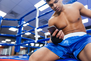 Boxer using smartphone in gym