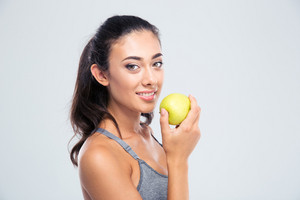 Smiling beautiful woman holding apple