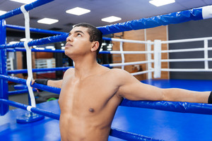 Pensive male boxer standing in gym