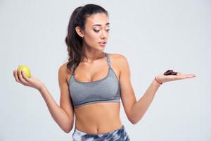 Woman choosing between apple or chocolate