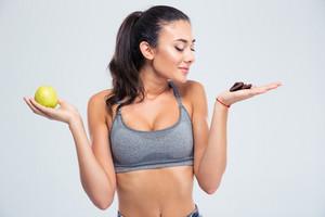 Girl choosing between apple or chocolate